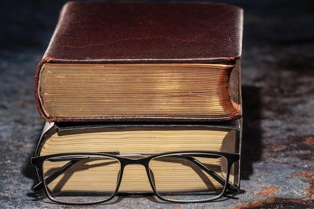 Un vecchio libro con gli occhiali. conoscenza e concetto di educazione.