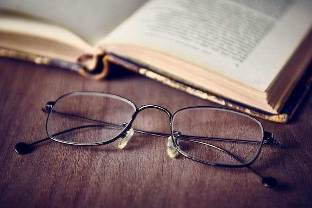 Vecchio libro con occhiali da lettura sulla scrivania in legno, dof poco profondo