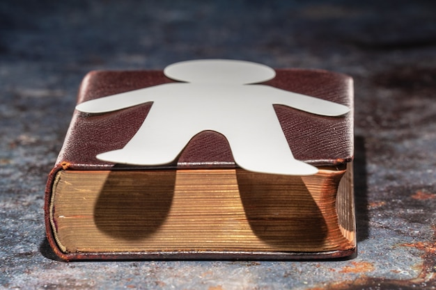 Un vecchio libro con la sagoma di un uomo sdraiato su di esso, fatto di carta. segnalibro.