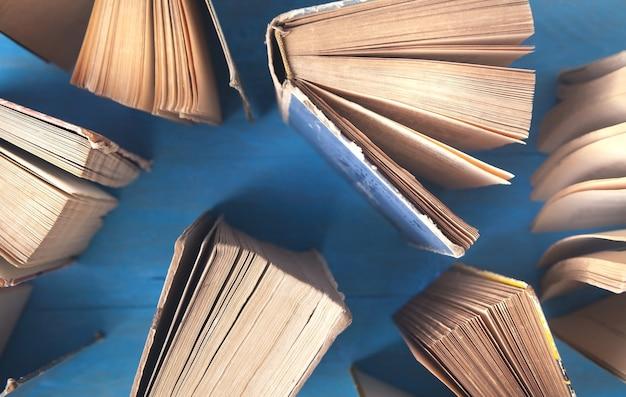 Vecchi libri sulla tavola di legno blu.