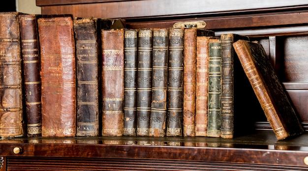 Vecchi libri posti sullo scaffale di legno