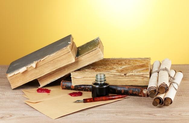 Vecchi libri, pergamene, penna a inchiostro e calamaio su tavola di legno su sfondo giallo
