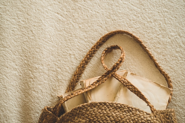 Vecchi libri e borsa di paglia dell'annata sulla coperta calda bianca. borsa donna estiva in paglia. borsa naturale marrone fatta a mano.