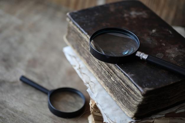 Vecchi libri su un tavolo di legno e lente d'ingrandimento in vetro