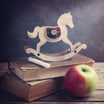 Vecchi libri e cavallo giocattolo in legno