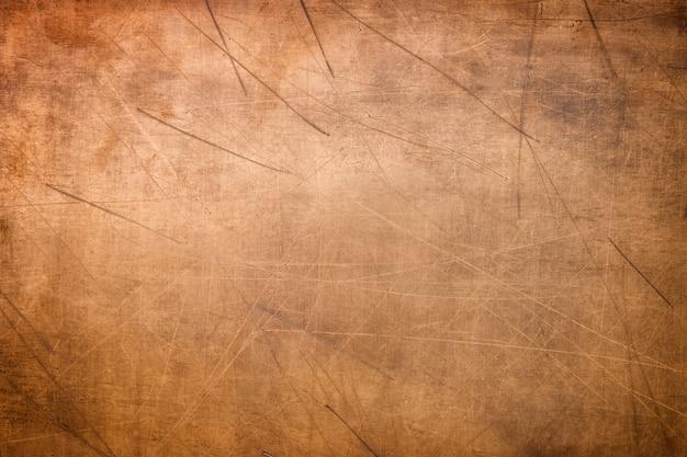 Vecchio fondo d'ottone o di rame, struttura di una placca di metallo arancio d'annata