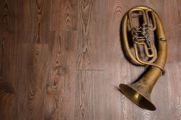 Vecchio corno d'ottone su fondo di legno