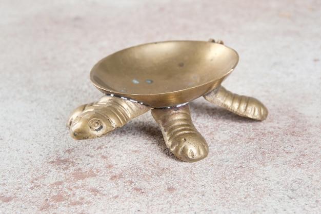 Vecchio posacenere tartaruga in ottone su sfondo di cemento. copia spazio e oggetti di scena fotografici.