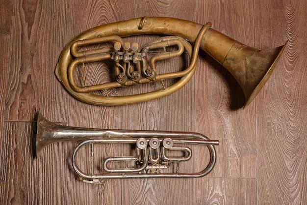 Vecchio strumento a fiato in ottone e corno su uno sfondo di legno.