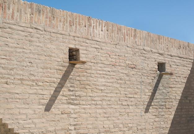 Vecchio muro di mattoni con uno scolo. antichi edifici dell'asia medievale. bukhara, uzbekistan