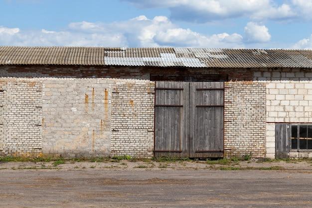 Vecchio magazzino in mattoni con grandi cancelli chiusi, cielo blu