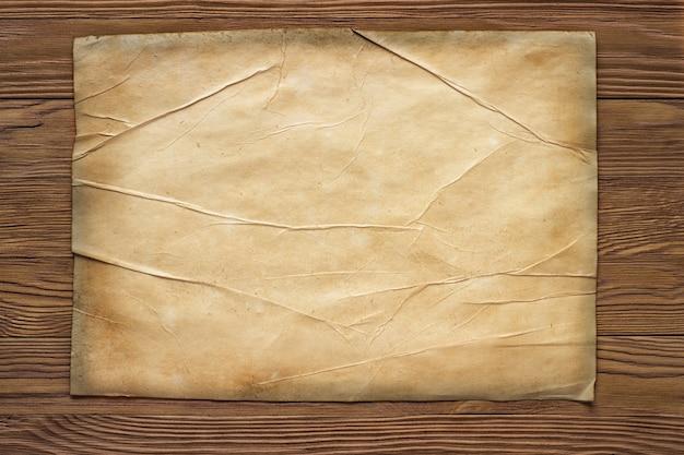 Vecchio foglio di carta orizzontale rotto sul bordo di legno marrone