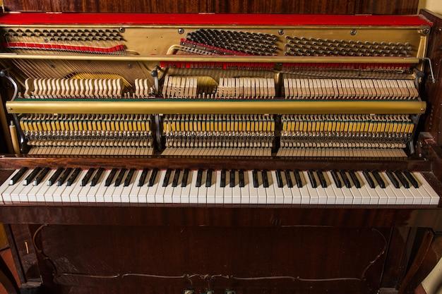 Vecchio pianoforte rotto in piedi al muro