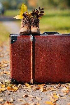 Vecchi stivali marroni con foglie all'interno sopra la valigia vintage marrone