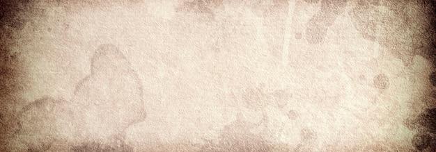 Un vecchio sfondo di carta marrone con macchie vintage malconce