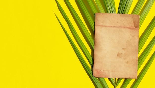 Vecchia carta marrone su foglie di palma tropicali su sfondo giallo.