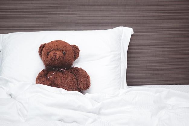 Il vecchio orsacchiotto marrone dorme sul cuscino, riposa e rilassa il concetto