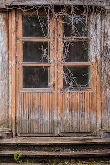 Vecchia porta di legno marrone con vetri delle finestre