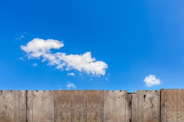 Vecchia staccionata in legno marrone con sfondo cielo