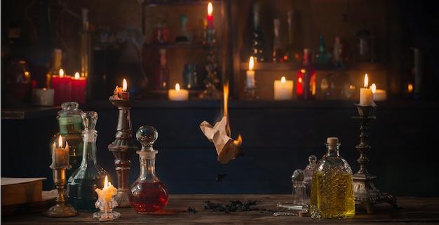 Vecchia carta in fiamme con pozioni sul vecchio tavolo in legno