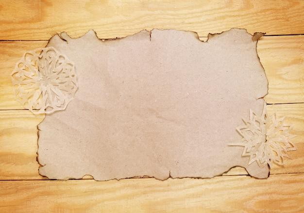Vecchia carta vuota bruciata e lavoro manuale di fiocchi di neve decorativi