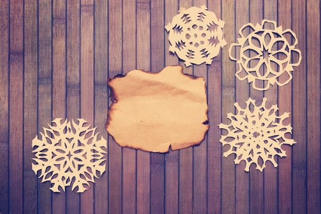 Vecchia carta vuota bruciata e fiocchi di neve decorativi
