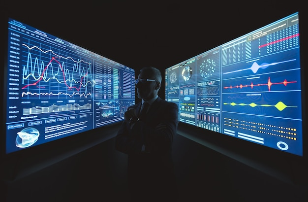 Il vecchio uomo d'affari in piedi vicino al grande schermo blu con la grafica