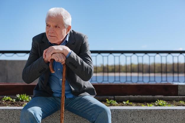 Vecchio cauto e triste uomo seduto su una pugnalata di cemento incrociando le mani mentre guarda i giovani