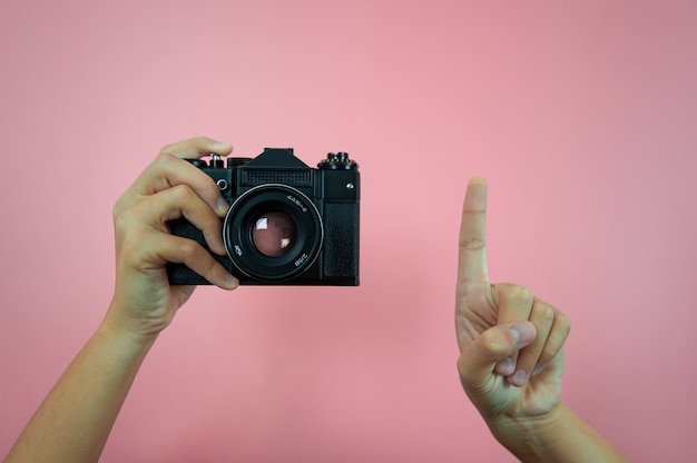 Vecchia macchina fotografica in mani femminili su uno sfondo rosa