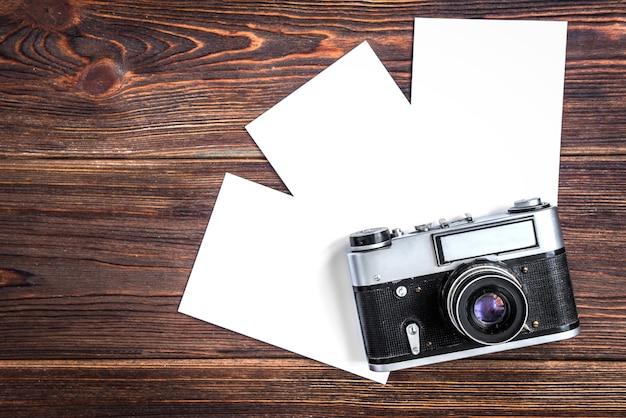 Vecchia macchina fotografica e carta fotografica in bianco su legno