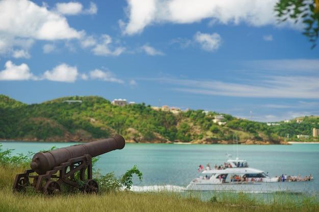 Il vecchio cannone nel forte sta guardando la barca con incredibili nuvole e isola sullo sfondo.