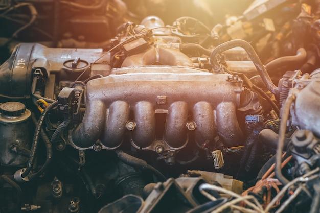 Vecchio pezzo di ricambio del motore dell'auto usato closeup collettore di scarico o intestazioni veicolo in acciaio macchina grasso sporco grunge con olio in garage per la vendita