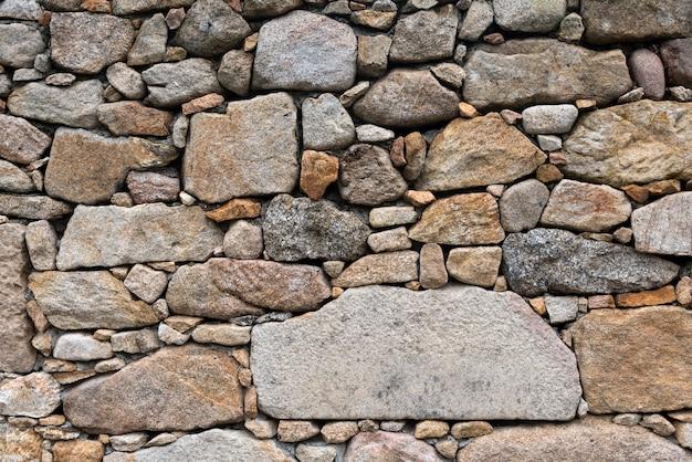 Fondo selvaggio della parete di pietra del vecchio castello