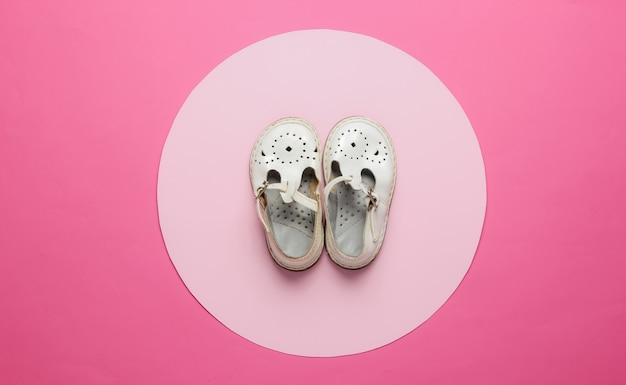 Vecchi sandali in pelle per bambini su sfondo rosa con colore pastello circleview