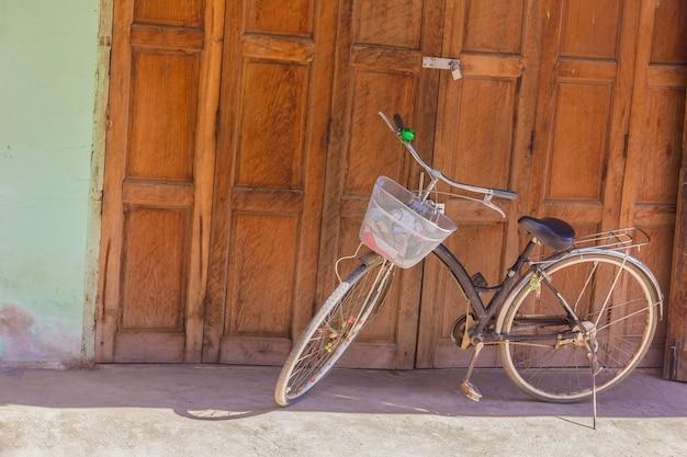 La vecchia bicicletta classica ha parcheggiato davanti alla vecchia parete di legno della plancia