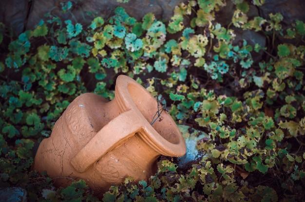 Vecchia anfora dell'argilla nella terra contro lo sfondo di erba verde.