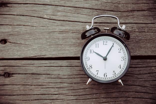 Vecchio orologio posto su sfondo di legno con spazio per il testo per il concetto di memoria dei tempi.