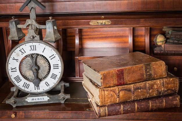 Vecchio orologio sullo scaffale con vecchi libri