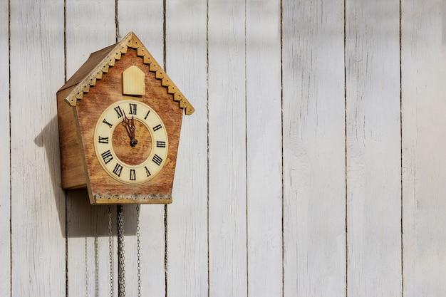Vecchio orologio su una parete leggera in legno. orologio vintage. orologio a cucù. copia-spazio.
