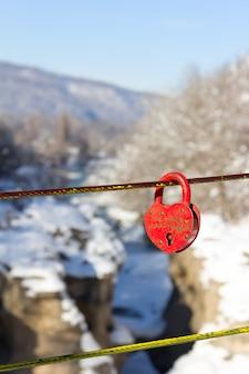 Vecchio lucchetto rosso chiuso nella forma del cuore su un fondo di una fine del canyon del fiume della montagna di inverno su