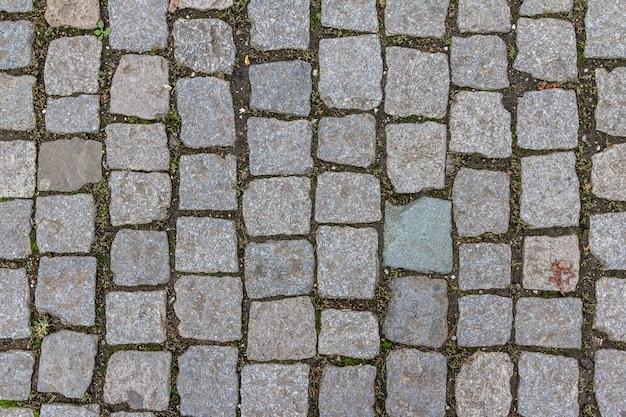 Vecchia struttura delle mattonelle di ciottoli nella città vecchia. modello astratto del mattone di pietra del granito. struttura del marciapiede di strada