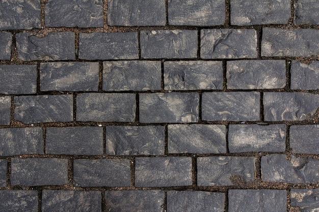 Vecchia struttura delle mattonelle di ciottoli nella città vecchia. priorità bassa della pavimentazione della città. struttura del marciapiede di strada.