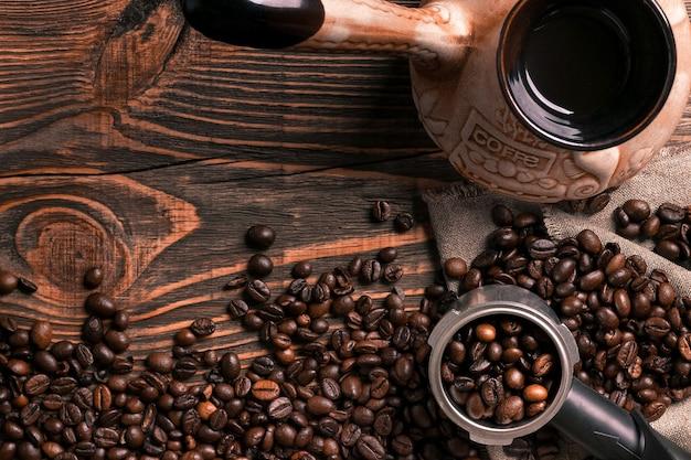 Vecchia tazza di caffè e turk con fagioli arrostiti su un tavolo di legno. concetto di aroma vintage su sfondo scuro.