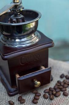 Vecchio macinino da caffè su uno sfondo di legno azzurro con chicchi di caffè sparsi. verticale.