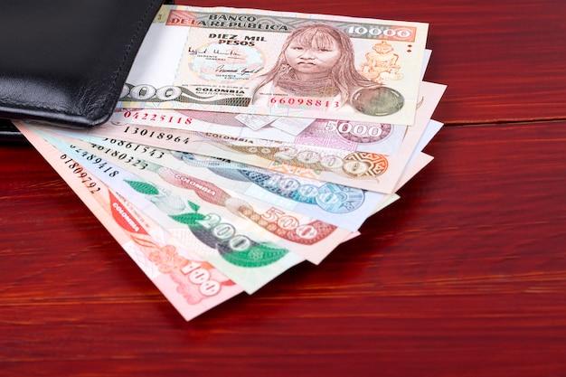 Vecchi soldi colombiani nel portafoglio nero