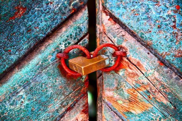 Vecchia porta colorata con vernice scrostata e lucchetto arrugginito