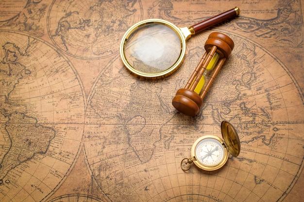 Vecchia bussola, lente d'ingrandimento e orologio della sabbia sulla mappa d'annata