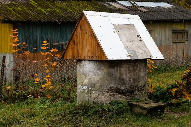 Vecchio pozzo di cemento con tetto di lamiera in un villaggio, vicino a una casa di paese