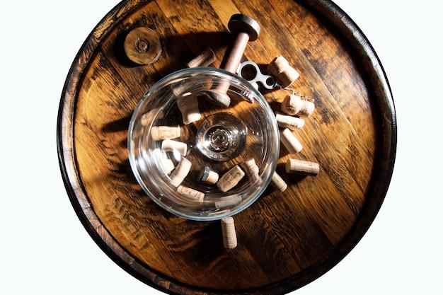 Un vecchio apribottiglie cavatappi e tappi di sughero in cima alla botte e vista dall'alto di bicchiere di vino vuoto, isolato