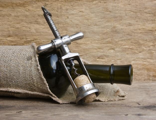 Vecchia cavatappi e bottiglia di vino sul tavolo